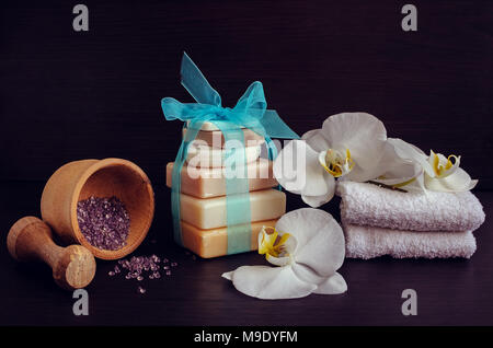 Composition of spa treatment on dark wooden background. Spa and wellness setting in white ans blue colors with natural homemade soaps, wooden pounder, - Stock Photo
