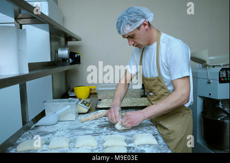 At the bakery: baker making buns on a work table. March 21, 2018. Brovary, Ukraine - Stock Photo
