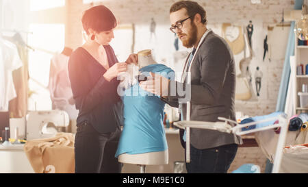 Male and Female fashion, designer, s are Working on Tailored Mannequin Wearing Clothes. They Also Use Smartphone. In Their Studio Sewing Machine - Stock Photo