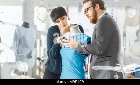 Male and Female fashion, designer, s are Working on Tailored Mannequin Wearing Clothes. They Consult Smartphone. In Their Studio Sewing Machine - Stock Photo
