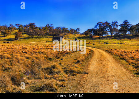 Remote abandoned farm in snowy mountains with empty stone hut building surrounded by plains and paddocks at the end of the road. - Stock Photo