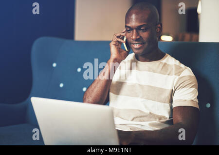 Smiling young African businessman working online with a laptop and talking on a cellphone while sitting on a sofa - Stock Photo