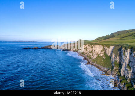 Northern Ireland, UK. Atlantic coast with cliffs and far aerial view of Carrick-a-Rede in County Antrim - Stock Photo