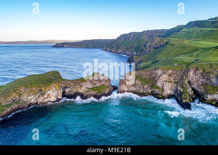 Northern Ireland, UK. Atlantic coast with cliffs and far aerial view of Carrick-a-Rede Rope Bridge in County Antrim - Stock Photo