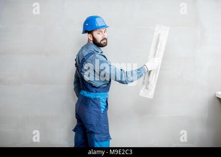 Plasterer working indoors - Stock Photo