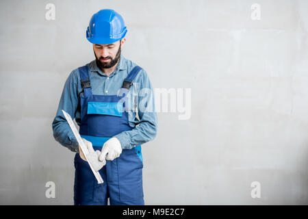 Plasterer with spatula indoors - Stock Photo