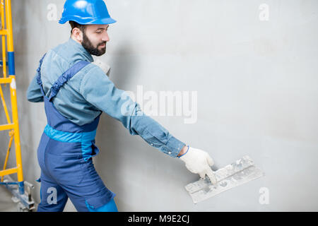 Plasterer working indoors - Stock Photo