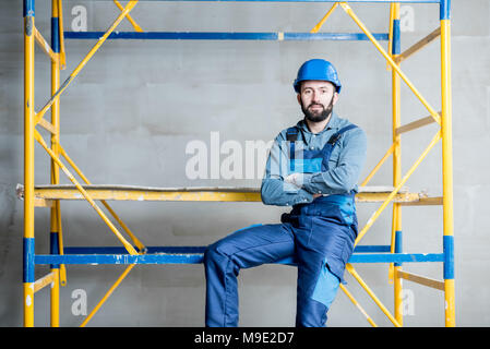 Builder on the scaffolding indoors - Stock Photo