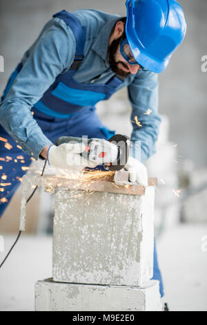 Builder cutting metal indoors - Stock Photo