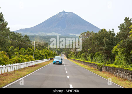 Blue car on the highway on the background of the volcano Pico, Azores - Stock Photo