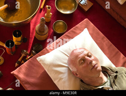 Een, Netherlands, September 18 - 2017: Sound healing session, senior man laying down on the floor in deep relaxation and with eyes closed, listening t - Stock Photo