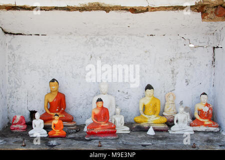 Different gypsum statuettes of Buddha in a dilapidated small roadside shrine in Sri Lanka - Stock Photo