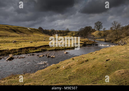 North Pennines landscape, East Mellwaters farm and Sleightholme Beck in a brief interval of late winter sunshine - Stock Photo
