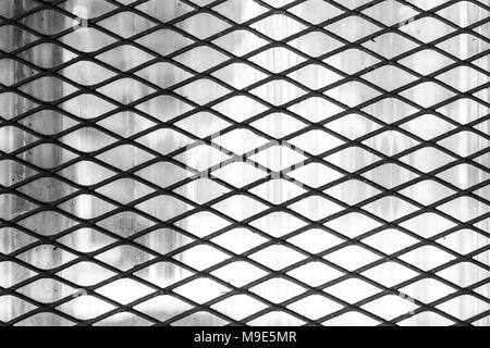 Dark metal wire protective diagonal grid or mesh, soft grey background. Black and white photo - Stock Photo