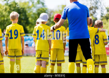 Youth football coach talking to childrens soccer team. Young football players with coach. Soccer coach coaching from the bench. - Stock Photo