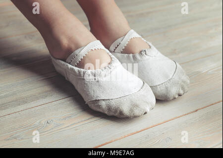 A little dancer. Legs of a girl in ballet slippers on a wooden floor - Stock Photo