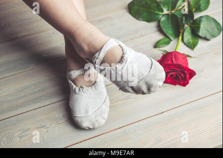 A little dancer and a red rose. Legs of a girl in ballet slippers on a wooden floor - Stock Photo