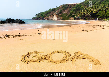 The inscription Goa on a sandy beach against the blue sea and the turquoise water and waves - Stock Photo