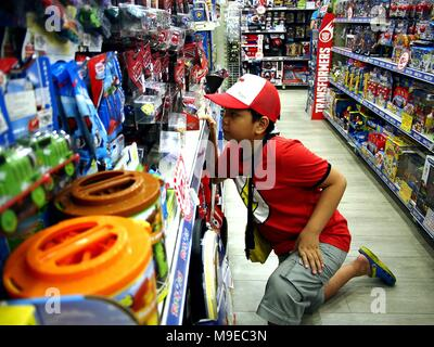QUEZON CITY, PHILIPPINES - MARCH 16, 2018: A boy looks at assorted toys on a shelf of a toy store. - Stock Photo
