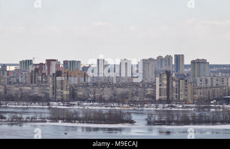 Kiev, March 24, 2018, Ukraine. View of the city and real estate through the winter river in the ice - Stock Photo