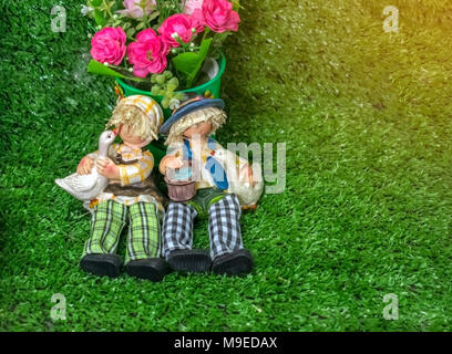 Ceramic dolls Couple sitting on green grass with pink flowers - Stock Photo
