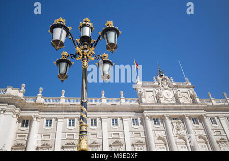 Ornate lamp post and facade of Palacio Real around Plaza de la Armeria - Stock Photo