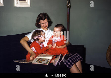 Two young children at bedtime wearing matching pyjamas sitting on their mother's lap on a sofa in a family living room with story books in the 1950s, USA. The little girl is laughing and has hair curlers in her hair. The baby boy is laughing at his sister - Stock Photo