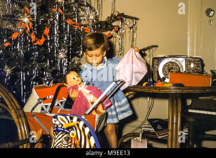 2 year old young girl playing with a doll and toy pram on Christmas Day, with a decorated Christmas tree in a family living room. Digital conversion of historical photo taken in Flushing, Queens, NYC, New York, USA, in 1957 - Stock Photo