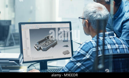 Two Senior Engineers Working With Detail Blueprint on a Personal Computer. They Actively Discuss Various Plans and Schemes. - Stock Photo