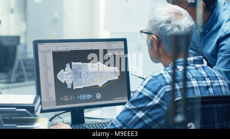 Two Senior Aircraft Engineers Working With Turbine Blueprint on a Personal Computer. They Actively Discuss Various Plans and Schemes. - Stock Photo