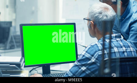 Two Senior Architectural Engineers Working With Green Screen on a Personal Computer. They Actively Discuss Various Plans and Schemes. Great Template - Stock Photo