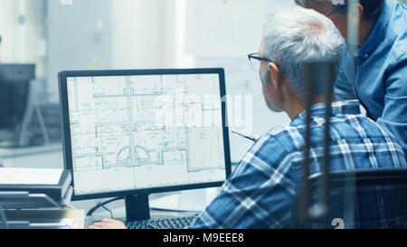 Two Senior Architectural Engineers Working With Building Blueprint on a Personal Computer. They Actively Discuss Various Plans and Schemes. - Stock Photo