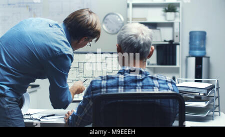 Two Senior Architectural Engineers Working With Building Plan on a Personal Computer. They Actively Discuss Various Plans and Schemes. - Stock Photo