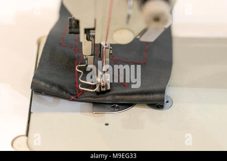 Closeup the sewing machine and item of clothing - Stock Photo