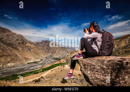 Dhankar gompa. Spiti Valley, Himachal Pradesh, India. Nature photographer tourist with camera shoots while standing on top of the mountain. - Stock Photo