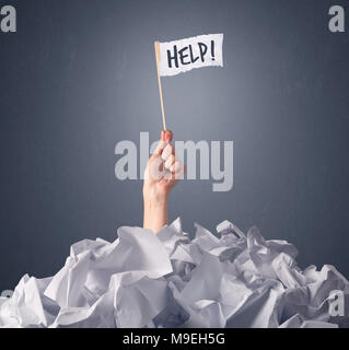 Female hand emerging from crumpled paper pile holding a white flag with help written on it - Stock Photo