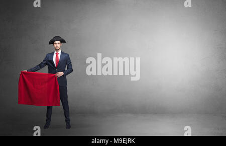 Businessman standing with red toreador cloth in his hand in an empty room  - Stock Photo