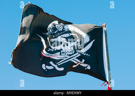 Black and white skull and crossbones pirate flag on a flagpole. - Stock Photo