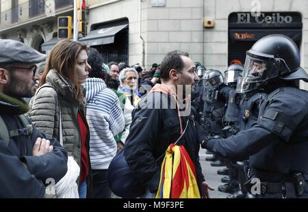 Catalonian riot police members face protesters during a protest called for by the Republican Defense Comittee (CDR) to protest against the detention of former Catalan leader Carles Puigdemont at the Spanish Government Delegation in the Autonomous Community of Catalonia in Barcelona, Catalonia, north eastern Spain, 25 March 2018. According to reports, German police on 25 March 2018 allegedly detained former Catalan leader Puigdemont after he crossed into Germany from Denmark. Puigdemont is sought by Spain who issued an European arrest warrant against the former leader who was living in exile in - Stock Photo