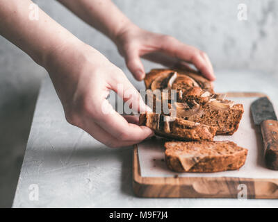 Butter-free,sugar-free banana bread with oat flour,soft curd cheese,honey. Woman hand with slice of banana bread on gray table. Ideas recipe healthy diet breakfast. Selective focus - Stock Photo
