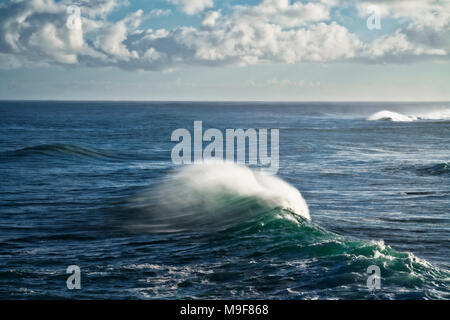 Large cresting waves with spindrift tails along the North Shore on Hawaii's Island of Kauai. - Stock Photo