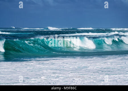 Large winter waves build and curl along Secret Beach on the North Shore of Hawaii's Island of Kauai. - Stock Photo