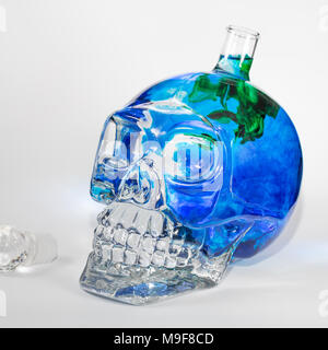 Glass skull with blue and green ink drops in water, alcohol - Stock Photo