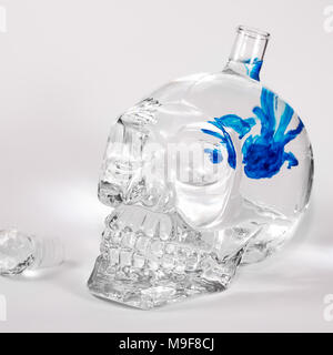 Glass skull with blue ink drops in water, alcohol - Stock Photo