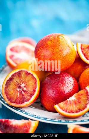 Sliced and whole fresh ripe juicy sicilian blood oranges - Stock Photo