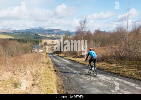 cyclist on the National Cycle Route 7, Old Drymen Road from Drymen heading towards Gartmore, Stirling, Scotland, UK - Stock Photo