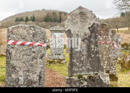 memorial safety - red and white hazard warning tape wrapped around headstones in Aberfoyle Old Parish Churchyard, Scotland, UK - Stock Photo