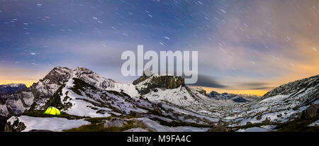 Panorama of illuminated tent under starry night sky in snowy alpine mountains. Alps, Switzerland. - Stock Photo
