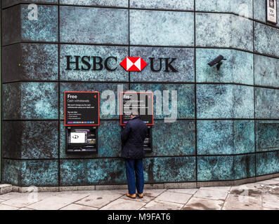 Rear view of a man withdrawing money from a HSBC Bank ATM, Queen Victoria Street, London, EC2, England, UK. - Stock Photo
