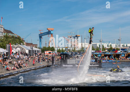 Flyboarder auf Wasserstrahl-Rückstoß, Jetski im Bootshafen, Kieler Woche, Kiel - Stock Photo